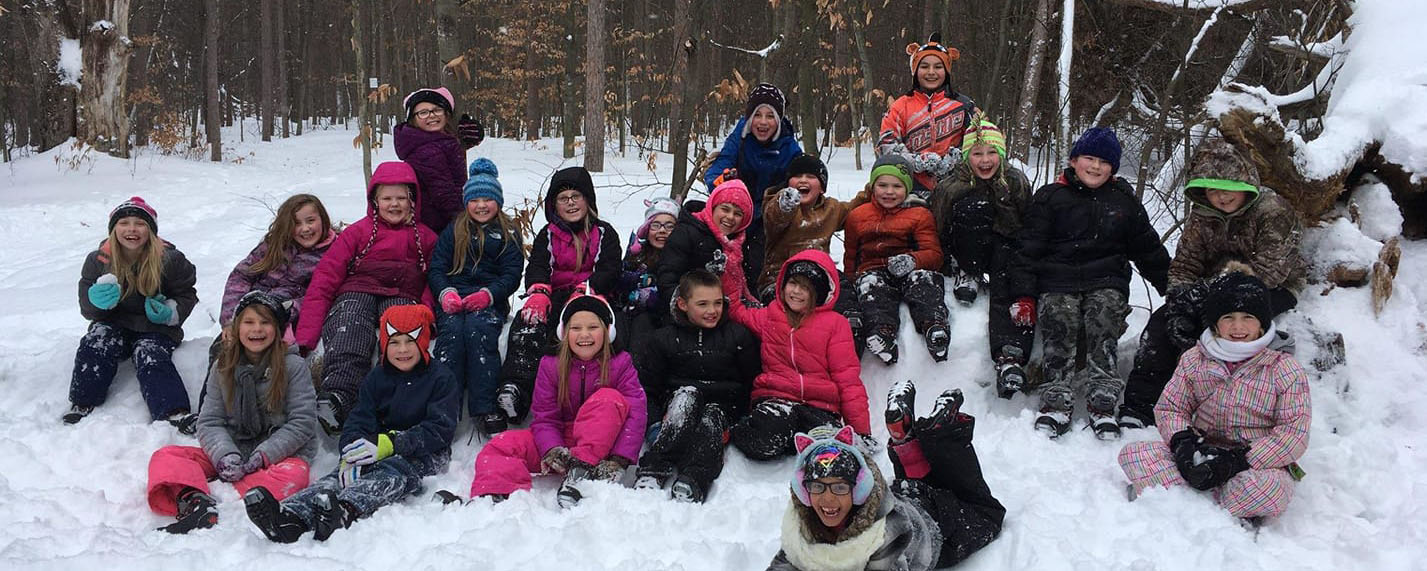group of 3rd graders sitting in the snow in front of a woods