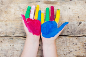 Colorful painted hands over the wooden background