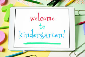 closeup of a tablet computer with the text welcome to kindergarten in its screen, on a desk full of numbers, pencil crayons of different colors and other stationery